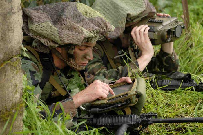 暗視装置などが組み込まれたターゲットロケーターを使用するイスラエル軍兵士(奥)と、PADでデータを送信する兵士t(手前)。自衛隊にはまだ導入されていない。